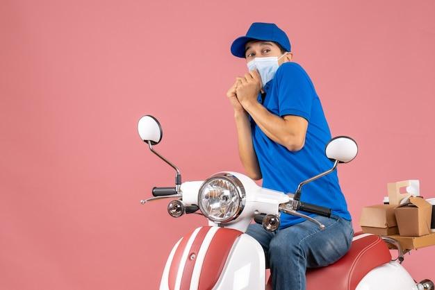 Draufsicht auf einen ängstlichen kurier in medizinischer maske mit hut, der auf einem roller sitzt und bestellungen auf pastellfarbenem pfirsichhintergrund liefert