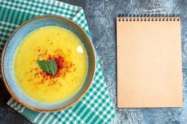 Draufsicht auf einen blauen topf mit leckerer suppe, serviert mit minze auf einem halb gefalteten, grün gestreiften handtuch neben einem spiralnotizbuch auf blauem hintergrund