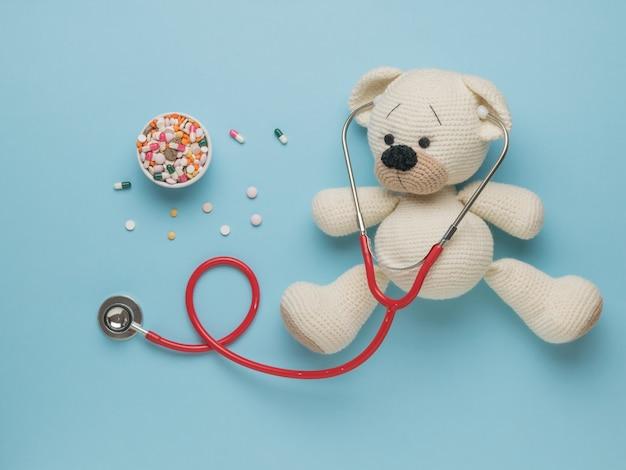 Draufsicht auf einen gestrickten bären und eine große anzahl von medikamenten auf blauem hintergrund.