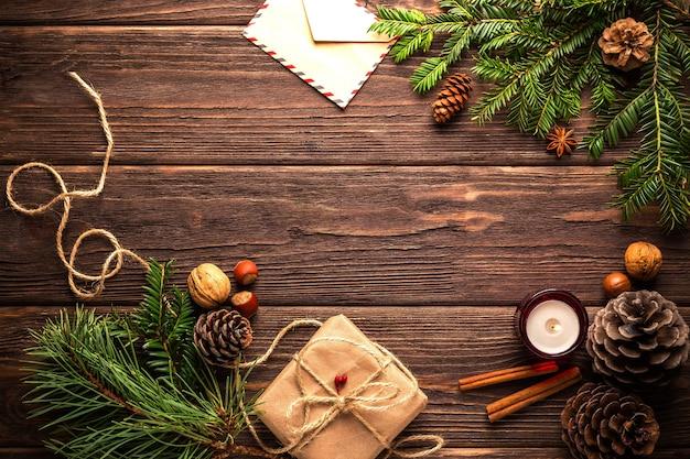 Draufsicht auf einen holztisch, der mit kiefernzweigen und kerzen für weihnachten verziert wird