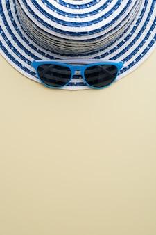 Draufsicht auf einen hut und eine blaue sonnenbrille auf einer beigen oberfläche