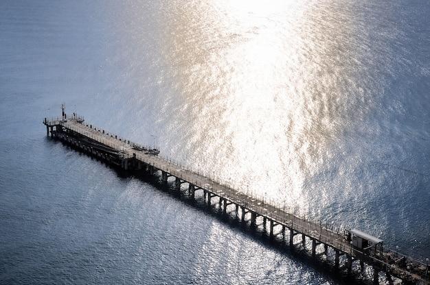 Draufsicht auf einen langen pier auf einer wand der meereswellen mit reflexion der sonne.
