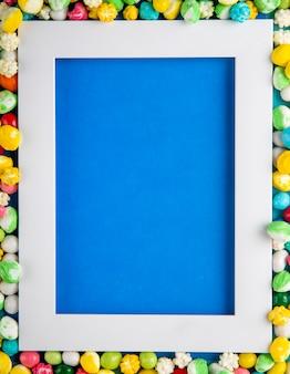 Draufsicht auf einen leeren bilderrahmen mit bunten bonbons, die auf blauem hintergrund angeordnet sind