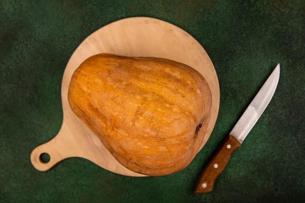 Draufsicht auf einen nahrhaften orangefarbenen gemüsekürbis lokalisiert auf einem hölzernen küchenbrett mit messer auf einer grünen wand