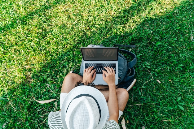 Draufsicht auf einen nicht erkennbaren jungen weißen digitalen nomaden, der aus der ferne an einem laptop arbeitet