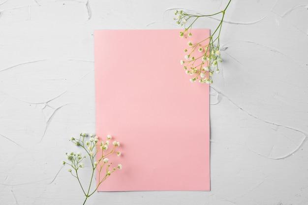Draufsicht auf einen rosa papierbrief und blumen mit kopienraum