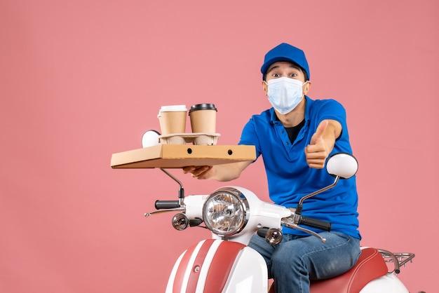 Draufsicht auf einen schockierten männlichen lieferer in maske mit hut, der auf einem roller sitzt und bestellungen auf pfirsich liefert