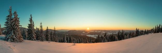Draufsicht auf einen schönen faszinierenden blick auf die skipiste mit skipisten in den bergen an einem sonnigen winterfrostabend. urlaubs- und tourismuskonzept im winter.