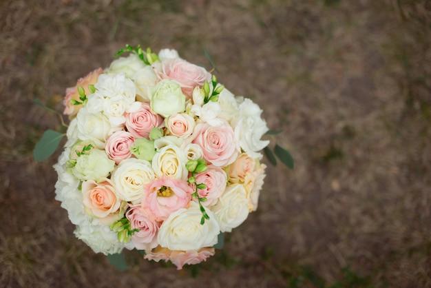 Draufsicht auf einen schönen zarten hochzeitsstrauß von cremefarbenen rosen und eustoma