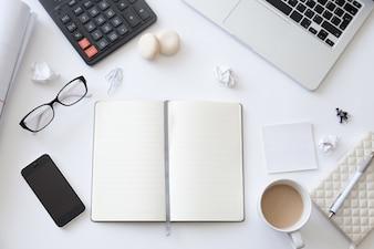 Draufsicht auf einen Schreibtisch mit offenem Notizbuch