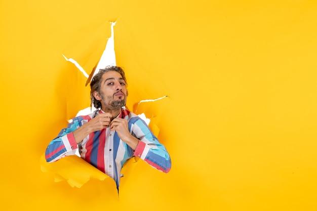 Draufsicht auf einen stolzen und ehrgeizigen jungen mann, der durch ein zerrissenes loch in gelbem papier für die kamera posiert