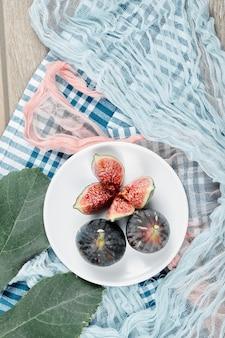Draufsicht auf einen teller mit ganzen und geschnittenen schwarzen feigen, einem blatt und blauen und rosa tischdecken auf holztisch.