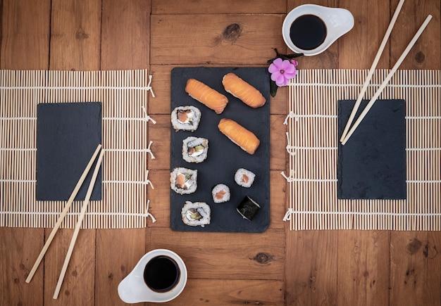 Draufsicht auf einen teller sushi und zwei plätze, die auf personen warten. rustikaler tisch aus recyceltem holz