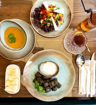 Draufsicht auf einen tisch, der zum abendessen mit dolma-sturz-suppe und gemüsesald serviert wird