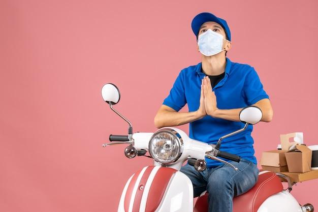 Draufsicht auf einen verträumten kurier in medizinischer maske mit hut, der auf einem roller sitzt und bestellungen auf pastellfarbenem pfirsichhintergrund liefert