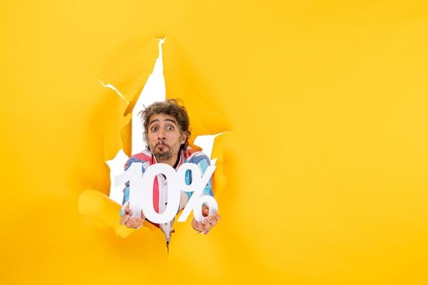Draufsicht auf einen verwirrten bärtigen mann, der zehn prozent in einem zerrissenen loch in gelbem papier zeigt