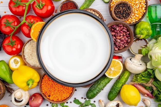 Draufsicht auf einen weißen topf auf der sammlung von frischem gemüse für das vegetarische abendessen