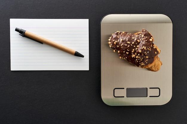 Draufsicht auf einige schokoladenbonbons auf einer küchenwaage, um die diät zu kontrollieren. konzept der ernährung und lebensmittelkontrolle.