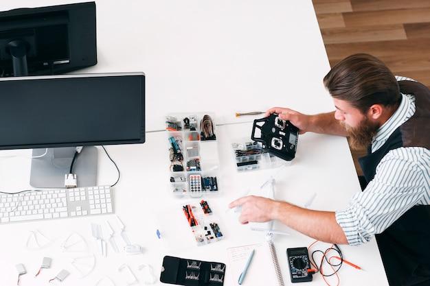 Draufsicht auf elektriker, der rc-sender befestigt. defekte renovierung der funksteuerung, reparaturwerkstatt für elektronisches spielzeug, freier platz für text auf weißem tisch