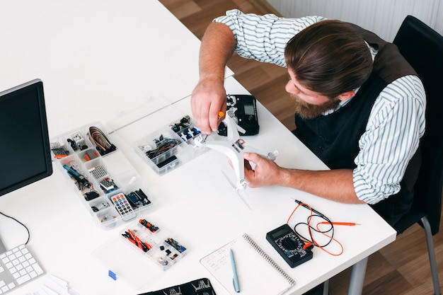 Draufsicht auf elektrikerarbeitsplatz mit werkzeugen, draufsicht. beschäftigter mechaniker, der kaputte drohne mit schraubendreher repariert. business, beruf, elektronikbaukonzept