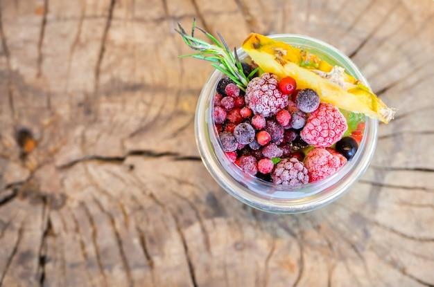 Draufsicht auf erfrischendes kühles getränk aus eistee mit gemischten beeren und einer scheibe ananasfrucht in einem plastikbecher auf holztisch on