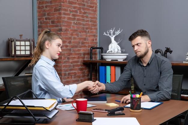 Draufsicht auf ernsthafte büroangestellte, die am tisch im besprechungsraum in der büroumgebung sitzen