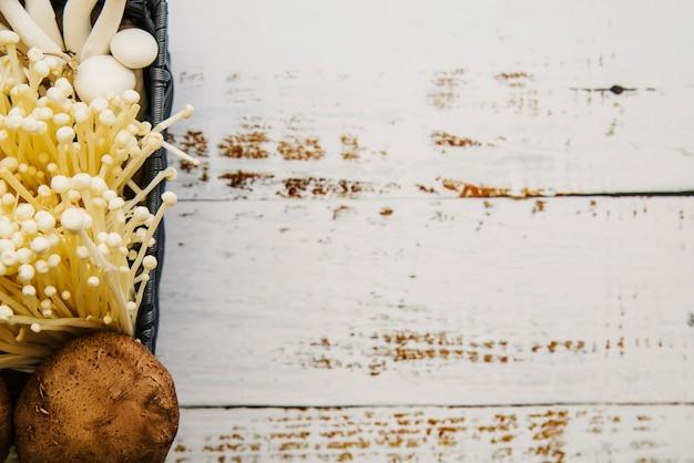 Draufsicht auf essbare pilze auf weißer planke