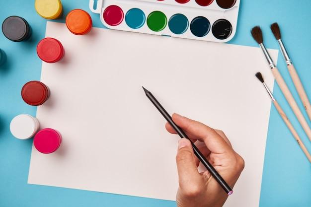 Draufsicht auf farbe und pinsel. leinwand verspotten. schultisch draufsicht. kunstunterricht