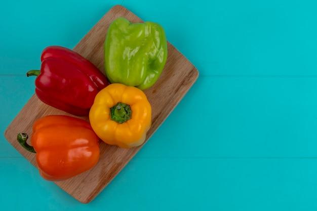 Draufsicht auf farbige paprika auf einem schneidebrett auf einer türkisfarbenen oberfläche