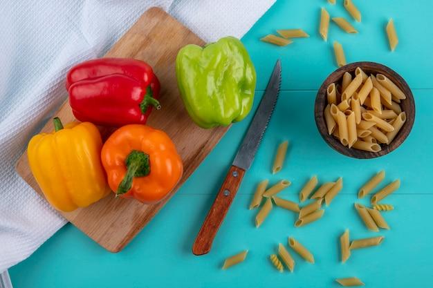Draufsicht auf farbige paprika auf einem schneidebrett mit rohen nudeln und einem messer auf einer türkisfarbenen oberfläche