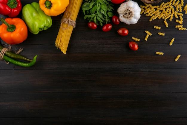 Draufsicht auf farbige paprika mit rohen spaghetti und nudelknoblauch und tomaten auf einer holzoberfläche