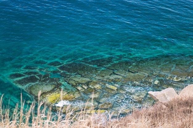 Draufsicht auf felsige küste und türkisfarbenes meerwasser