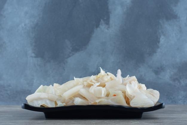 Draufsicht auf fermentierten kohl auf schwarzem teller