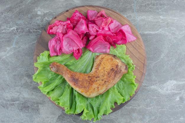 Draufsicht auf fermentierten kohl mit gebratenem hühnerbein mit salatblatt.