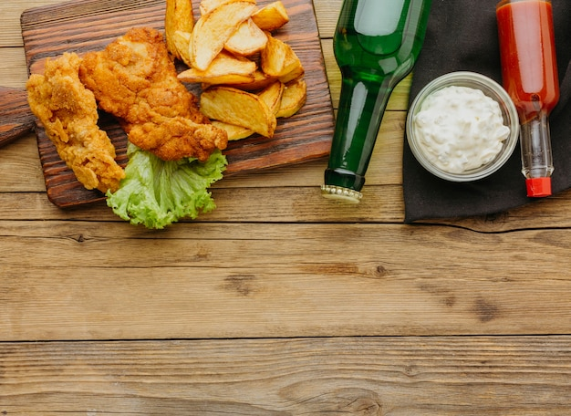Draufsicht auf fisch und chips mit soße und ketchup und bierflaschen