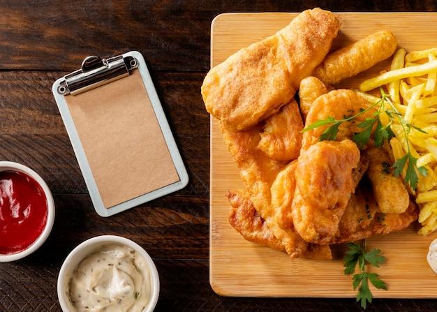 Draufsicht auf fish and chips mit klemmbrett und saucen