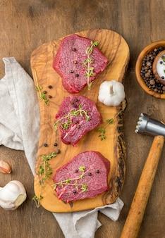 Draufsicht auf fleisch mit knoblauch und kräutern