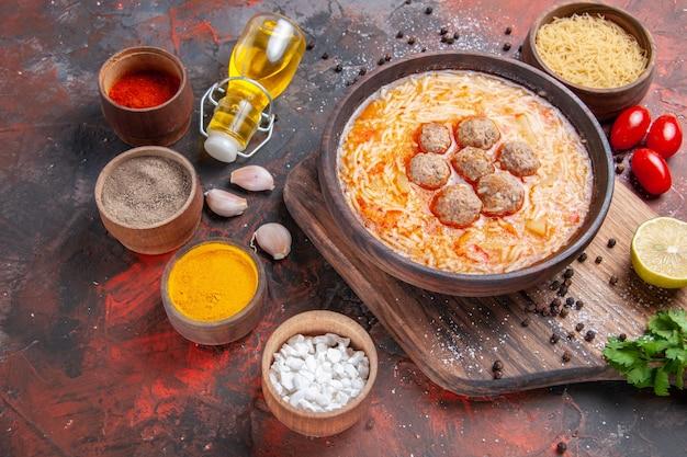 Draufsicht auf fleischbällchensuppe mit nudeln ungekochtes pasta-schneidebrett zitrone ein bündel grüne tomaten verschiedene gewürze auf dunklem tisch