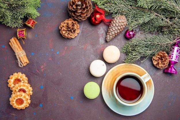 Draufsicht auf französische macarons mit keksen und tee auf schwarz