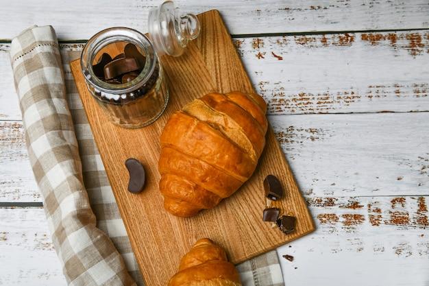 Draufsicht auf französische schokoladencroissants. der anfang des morgens. frisches französisches croissant. kaffeetasse und frisch gebackene croissants auf einem holz. .