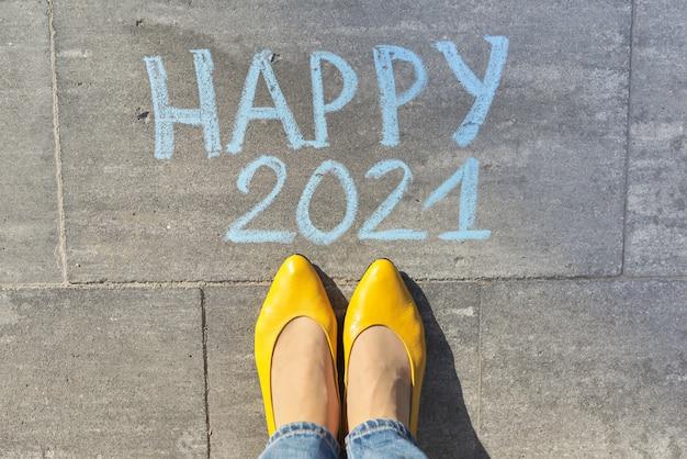 Draufsicht auf frauenbeine und glücklichen 2021 text geschrieben in kreide auf grauem bürgersteig
