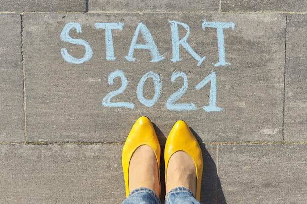 Draufsicht auf frauenbeine und start 2021 text in kreide auf grauem bürgersteig geschrieben