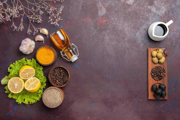 Draufsicht auf frisch geschnittene zitrone mit grünem salat und oliven auf schwarz