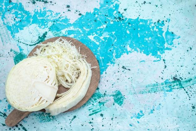 Draufsicht auf frisch geschnittenen kohl, der auf hellblauem gemüsesalat mit gesundem gemüsesnack zusammengesetzt und halb ganz ist