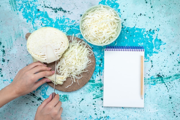 Draufsicht auf frisch geschnittenen kohl mit halb ganzem gemüse, das geschnitten wird und notizblock auf hellblauem schreibtisch, gemüsesalatmahlzeit-gesunder salat