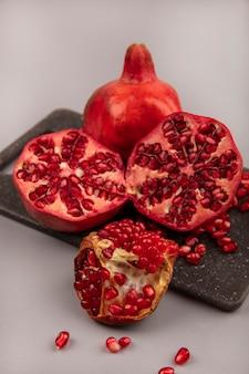 Draufsicht auf frisch halbierte und ganze granatäpfel auf einem schwarzen küchenbrett