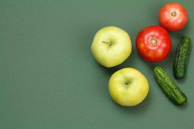 Draufsicht auf frische äpfel, tomaten und gurken auf grünem hintergrund. gemüse und obst auf dem küchentisch.