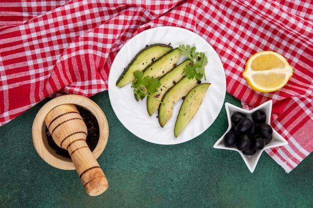 Draufsicht auf frische avocado-scheiben auf weißem teller mit schwarzen oliven mit holzmörser und stößel auf rot karierter tischdecke und grün
