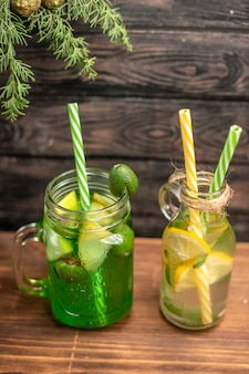 Draufsicht auf frische bio-säfte in flaschen mit tuben und früchten auf einem braunen tisch