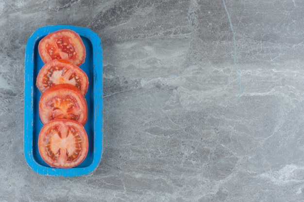 Draufsicht auf frische bio-tomatenscheiben auf blauem holzbrett